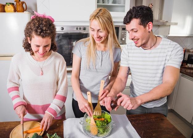 Amigos do sexo feminino felizes preparando a salada na cozinha