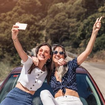 Amigos do sexo feminino felizes sentado no capô do carro, tendo auto-retrato no smartphone