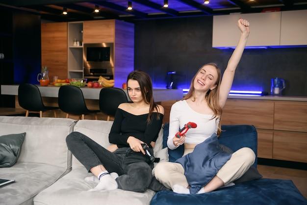 Amigos do sexo feminino jovens alegres e bonitos, sentado no sofá no apartamento contemporâneo e desfrutando de jogos de vídeo