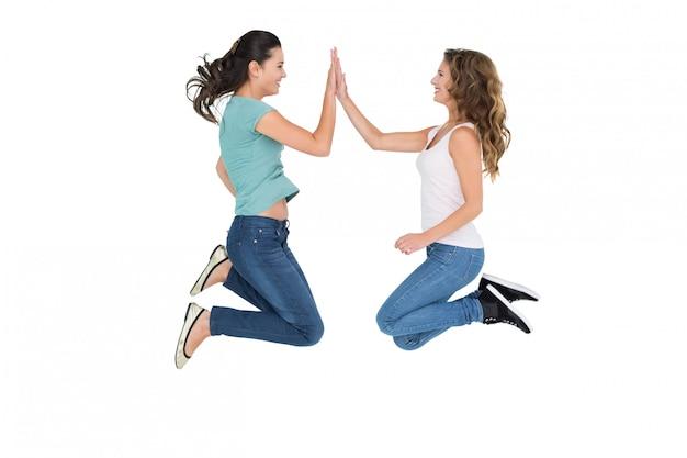 Amigos do sexo feminino jovens felizes jogando jogo de palmas