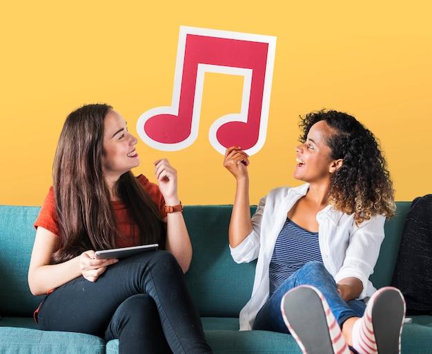 Amigos do sexo feminino jovens segurando um ícone de nota musical