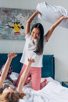 Amigos do sexo feminino lutando por travesseiros