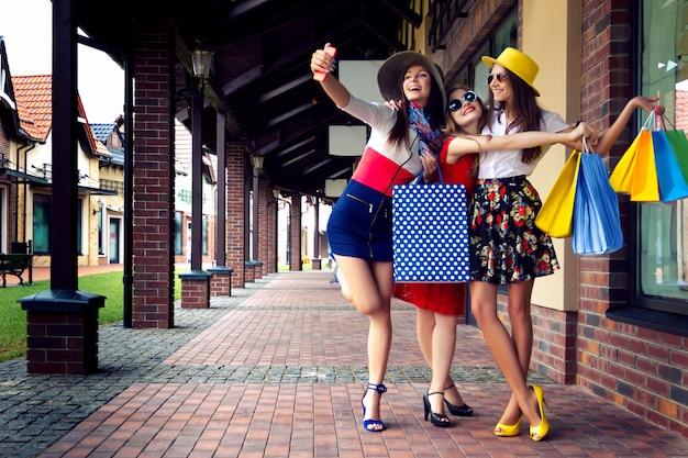Amigos do sexo feminino muito felizes mulheres brilhantes em vestidos coloridos, chapéus e sapatos de salto altos com sacos de compras, fazendo selfie depois das compras