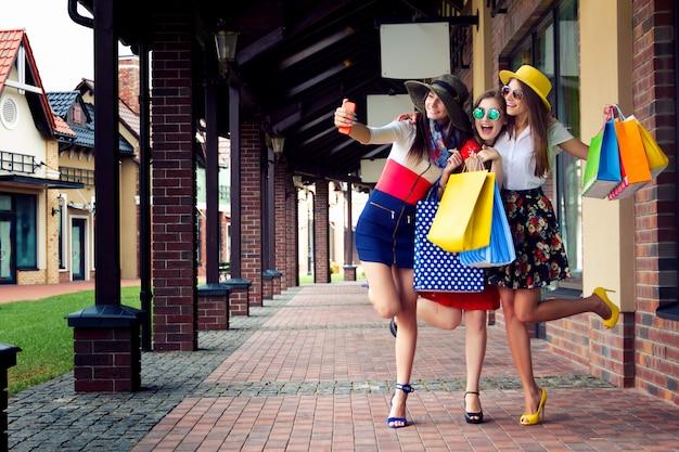Amigos do sexo feminino muito felizes mulheres brilhantes em vestidos coloridos, chapéus e sapatos de salto altos com sacos de compras, fazendo selfie