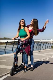 Amigos do sexo feminino muito jovens, montando uma scooter elétrica na rua