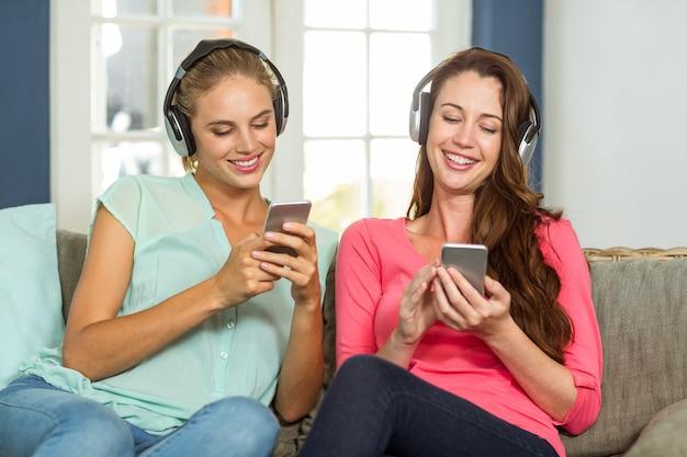 Amigos do sexo feminino ouvindo música em casa
