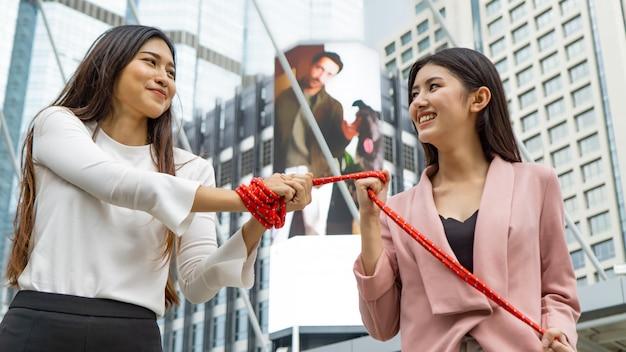 Amigos do sexo feminino segurando a corda enquanto caminhava na rua