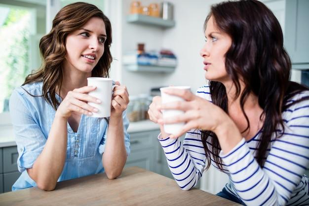 Amigos do sexo feminino segurando canecas de café enquanto discutia na mesa