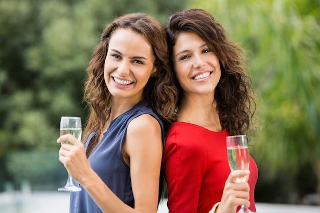 Amigos do sexo feminino segurando taças de champagne a sorrir