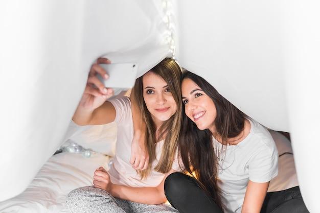 Amigos do sexo feminino sentado na cama, tendo selfie no smartphone sob a cortina