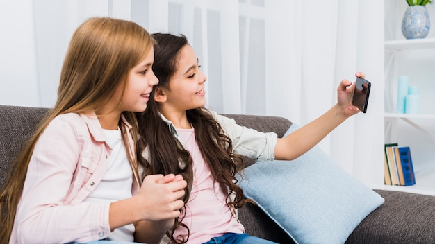 Amigos do sexo feminino sentado no sofá tomando selfie no telefone inteligente