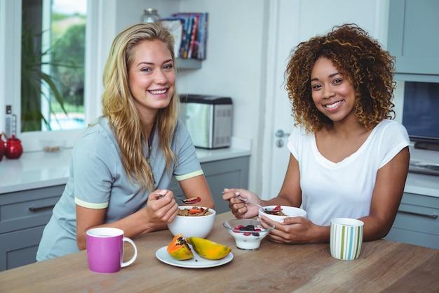 Amigos do sexo feminino sorrindo enquanto tomando café na cozinha