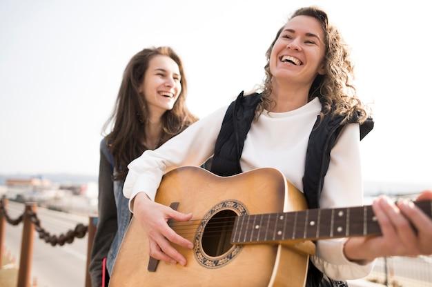 Amigos do sexo feminino tocando violão