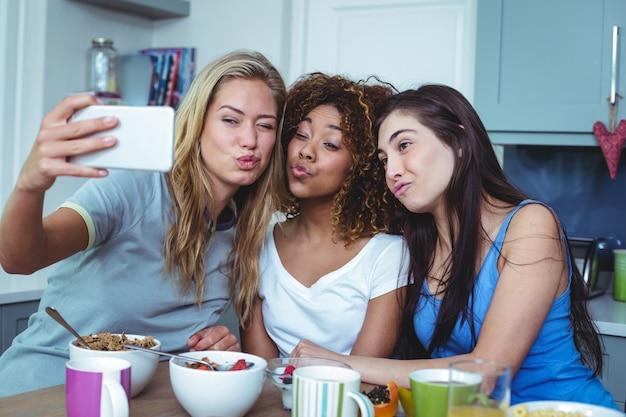 Amigos do sexo feminino tomando auto-retrato a sorrir