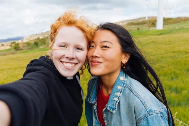 Amigos do sexo feminino tomando selfie no parque eólico