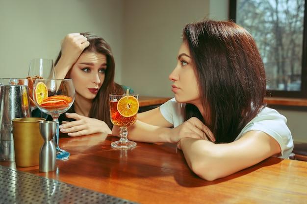 Amigos do sexo feminino tomando uma bebida no bar. eles estão sentados em uma mesa de madeira com coquetéis. eles estão vestindo roupas casuais.