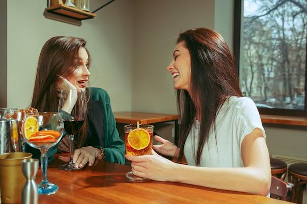 Amigos do sexo feminino tomando uma bebida no bar. eles estão sentados em uma mesa de madeira com coquetéis.