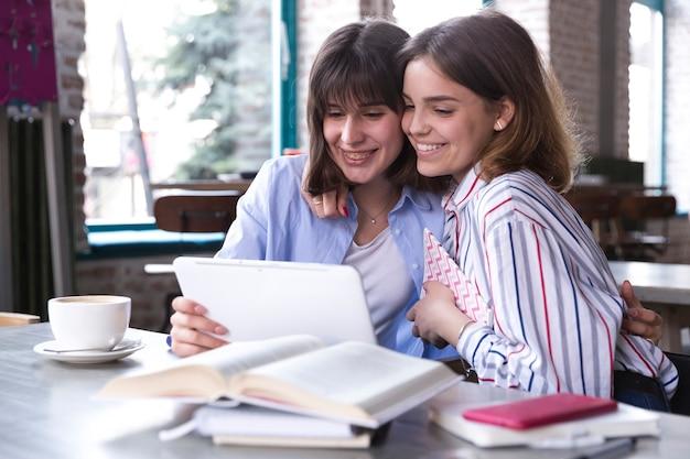 Amigos do sexo feminino usando tablet juntos