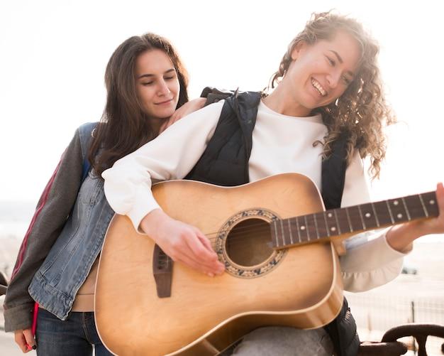 Amigos do sexo feminino vista baixa tocando violão
