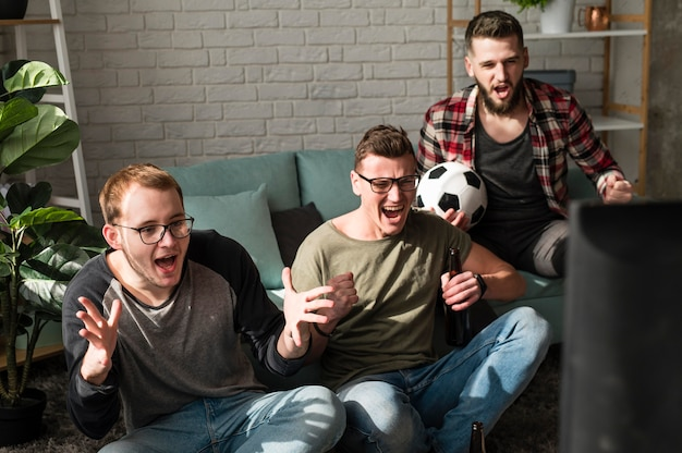 Amigos do sexo masculino alegres assistindo esportes na tv com futebol
