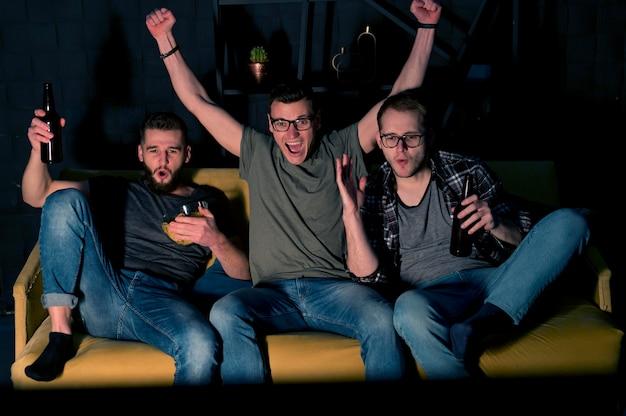 Amigos do sexo masculino alegres assistindo esportes na tv enquanto tomam uma cerveja