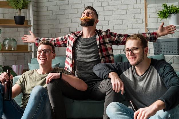 Amigos do sexo masculino alegres comendo pizza e cerveja e assistindo esportes na tv