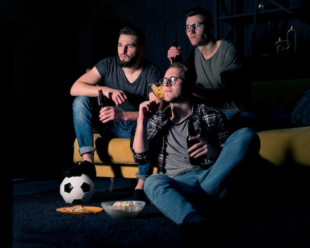 Amigos do sexo masculino assistindo esportes na tv juntos, enquanto bebem cerveja e lanches