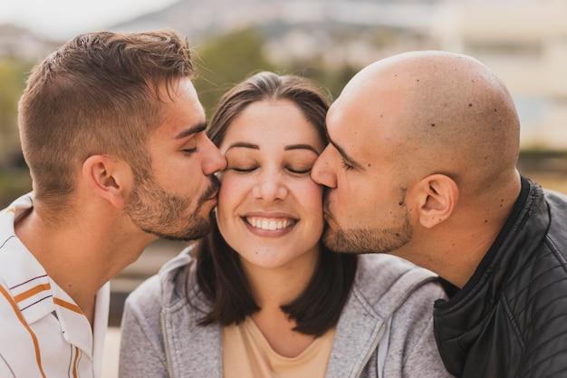 Amigos do sexo masculino beijando mulher