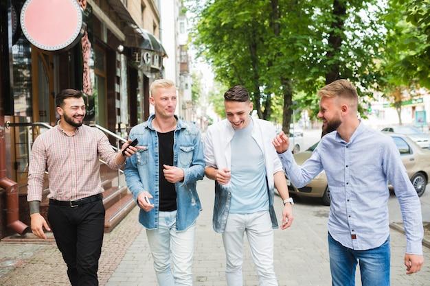 Amigos do sexo masculino caminhando juntos na rua da cidade apreciando