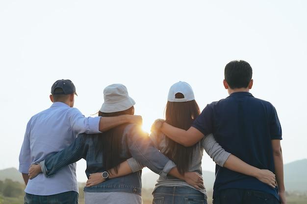 Amigos do sexo masculino e feminino se abraçando, olhando para os conceitos da comunidade de amizade ao nascer do sol