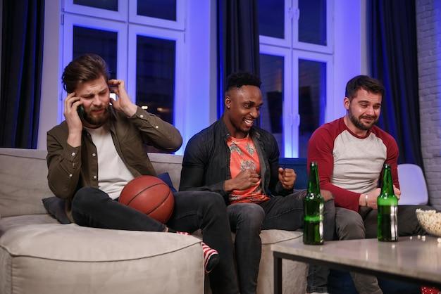 Amigos do sexo masculino incentivando com grita seu time favorito e interferindo no amigo para ter uma conversa móvel