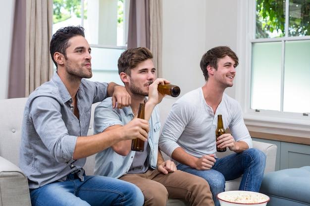 Amigos do sexo masculino jovens bebendo cerveja enquanto assiste tv