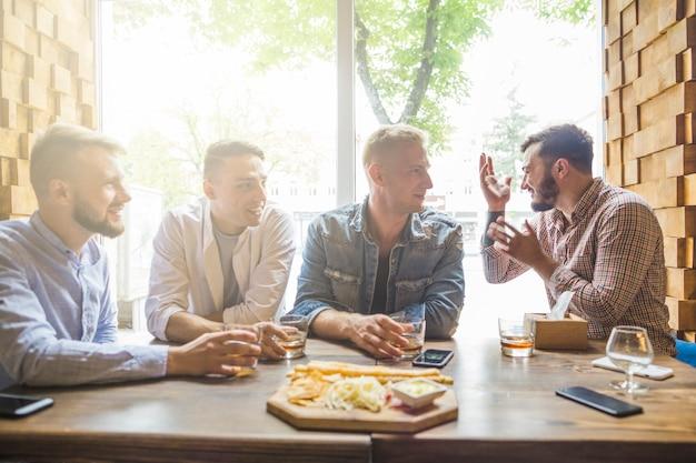 Amigos do sexo masculino jovens sentados no restaurante apreciando as bebidas