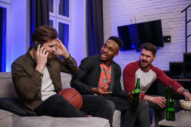 Amigos do sexo masculino multirraciais, barulhentos e agradáveis, ferozes, incentivando com gritos o seu time de futebol favorito e interferindo no amigo para ter uma conversa móvel