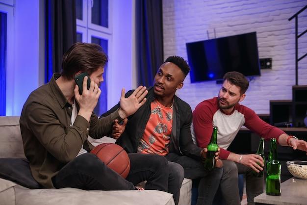 Amigos do sexo masculino multirraciais, barulhentos e ferozes, simpáticos, incentivando com gritos seu time favorito e interferindo com seu amigo para ter uma conversa móvel