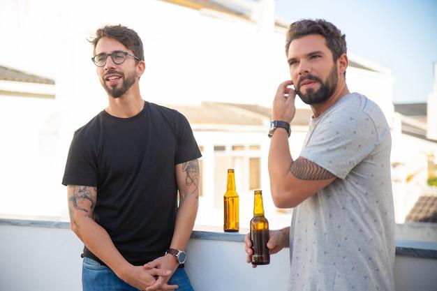 Amigos do sexo masculino olhando para longe enquanto bebe cerveja