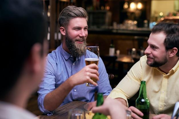 Amigos do sexo masculino passando um tempo juntos no bar