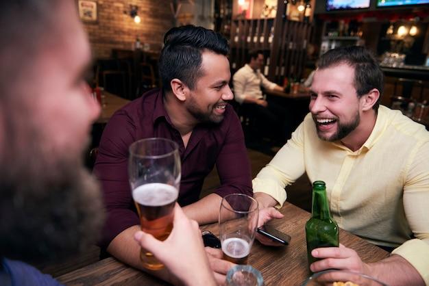 Amigos do sexo masculino relaxando com bebidas no bar