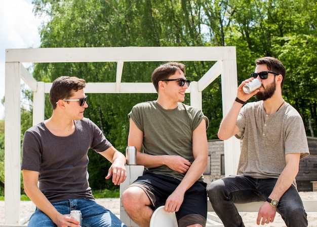 Amigos do sexo masculino relaxantes com bebidas refrescantes