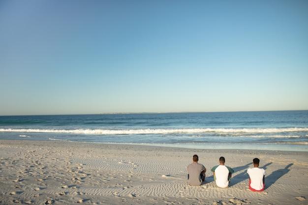 Amigos do sexo masculino relaxantes juntos na praia