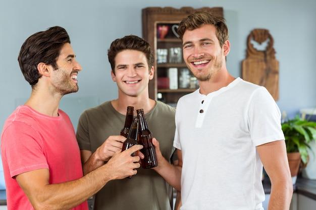 Amigos do sexo masculino sorridentes brindando a garrafas de cerveja