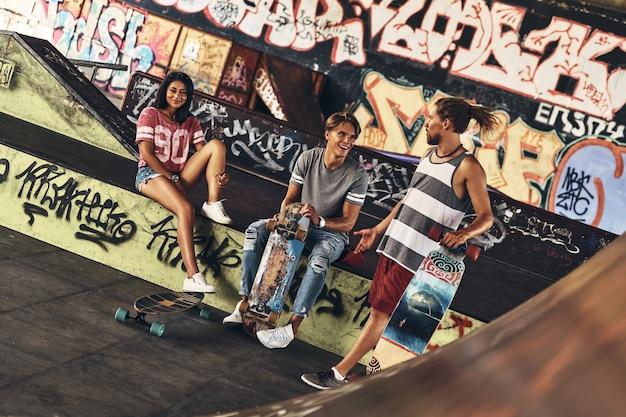 Amigos do skate para sempre. grupo de jovens modernos saindo juntos enquanto passam o tempo na pista de skate ao ar livre