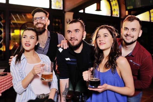 Amigos dos fan de futebol ou fãs que olham o futebol em uma barra de esportes que guarda canecas de cerveja.