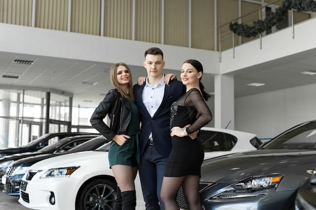 Amigos, duas mulheres e um homem se abraçam contra carros novos em uma concessionária de carros.