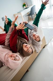 Amigos e mulheres asiáticas hijab deitam e levantam as mãos na cama enquanto tiram uma selfie juntos