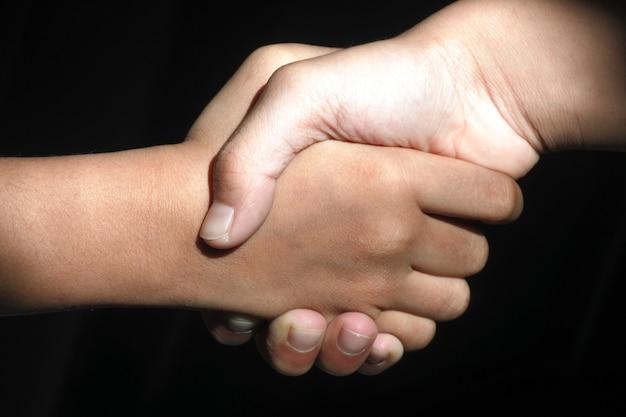 Amigos e parceiros apertando as mãos com fundo escuro. conceito de perdão e saudação