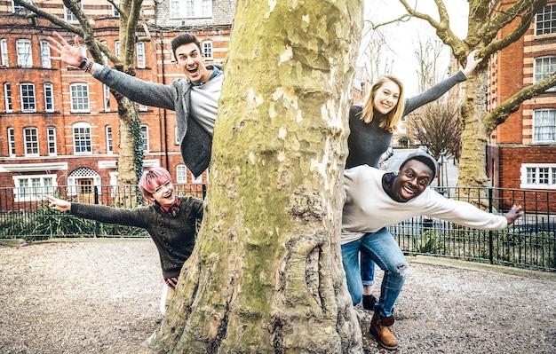 Amigos elegantes multirraciais se divertindo ao ar livre no parque da cidade em shoreditch, londres