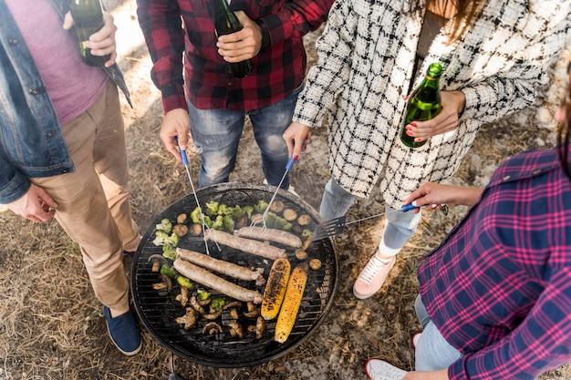 Amigos em alto ângulo fazendo churrasco com cervejas