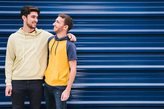 Amigos em camisolas de pé e abraçando