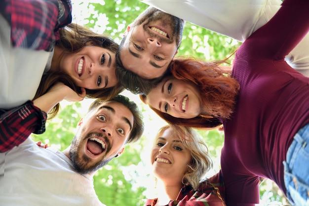 Amigos em círculo com as cabeças juntas, sorrindo